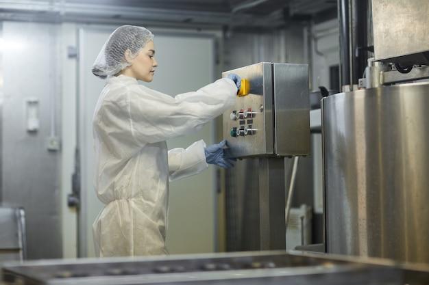 Retrato de vista lateral de uma jovem trabalhadora operando unidades de máquina na fábrica de produção de alimentos limpos, copie o espaço