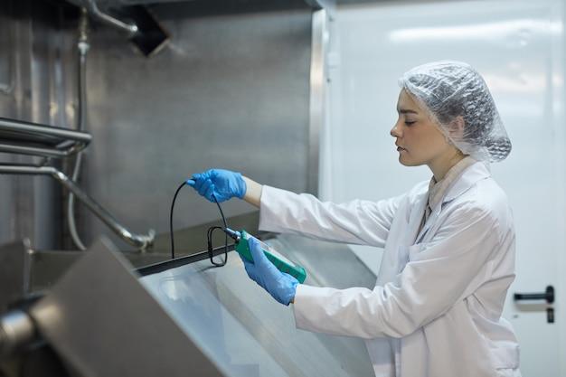 Retrato de vista lateral de uma jovem trabalhadora segurando um medidor de temperatura enquanto examina uma mistura em uma fábrica de alimentos industrial, copie o espaço