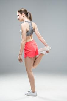 Retrato de vista lateral de uma mulher jovem fitness em pé e esticando as pernas