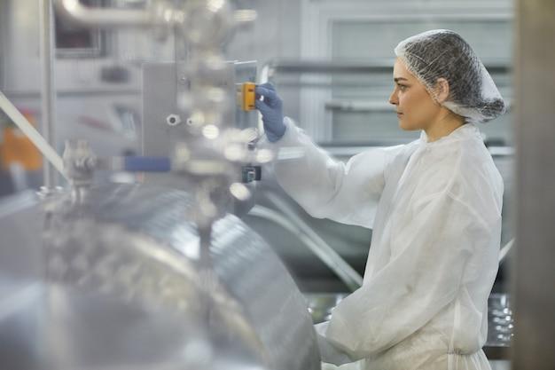 Retrato de vista lateral de uma trabalhadora apertando o botão enquanto opera unidades de máquina na fábrica de produção de alimentos limpos, copie o espaço