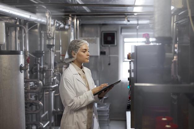 Retrato de vista lateral de uma trabalhadora segurando um tablet digital durante a inspeção de controle de qualidade na oficina de uma fábrica de alimentos, copie o espaço