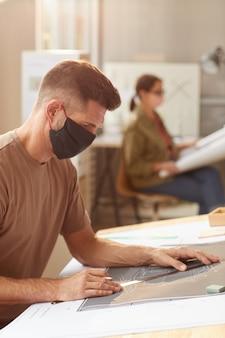Retrato de vista lateral do arquiteto barbudo maduro usando máscara enquanto está sentado na mesa de desenho sob a luz do sol