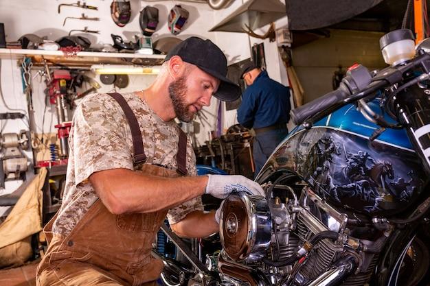 Retrato de vista lateral do homem que trabalha na garagem, reparação de moto