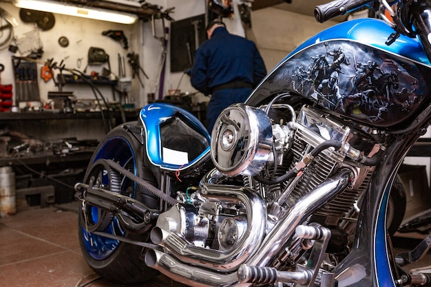 Retrato de vista lateral do homem trabalhando na garagem, reparando a motocicleta e personalizando-o