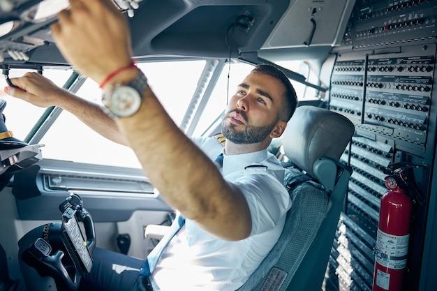 Retrato de vista lateral do piloto de uniforme, apertando botões na cabine principal do avião de passageiros