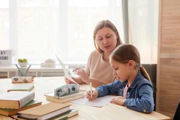 Retrato de vista lateral em tons quentes de uma linda garotinha escrita teste enquanto estudava em casa com a mãe ou o tutor ajudando-a