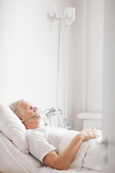 Retrato de vista lateral vertical de homem idoso doente deitado em uma cama de hospital com máscara de suplementação de oxigênio e olhos fechados, copie o espaço