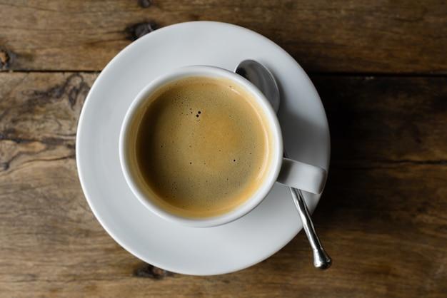 Retrato de vista superior de café quente contra uma velha mesa de madeira