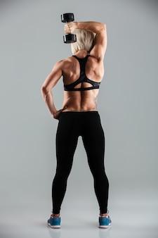 Retrato de vista traseira de comprimento total de uma desportista de ajuste muscular
