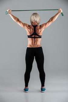 Retrato de vista traseira de comprimento total de uma desportista muscular adulta
