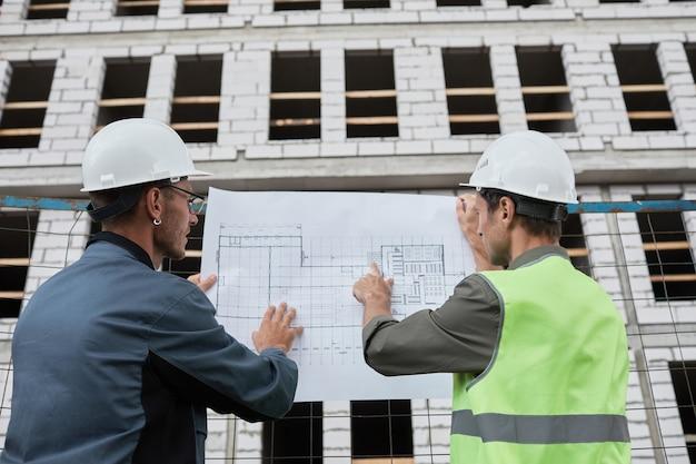 Retrato de vista traseira de dois engenheiros discutindo plantas baixas no canteiro de obras