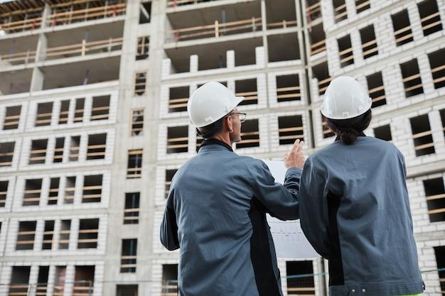 Retrato de vista traseira de dois engenheiros discutindo plantas baixas no espaço de cópia do canteiro de obras