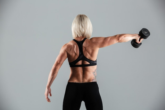 Retrato de vista traseira de uma desportista muscular em forma
