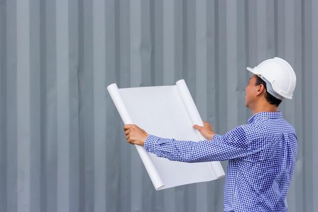 Retrato de vista traseira do engenheiro asiático segurando planos contra a parede em pé no canteiro de obras, copie o espaço