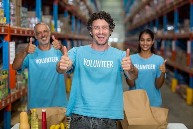 Retrato de voluntários, mostrando os polegares