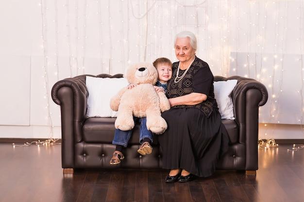 Retrato de vovó feliz e seu neto abraçando, olhando para a câmera e sorrindo