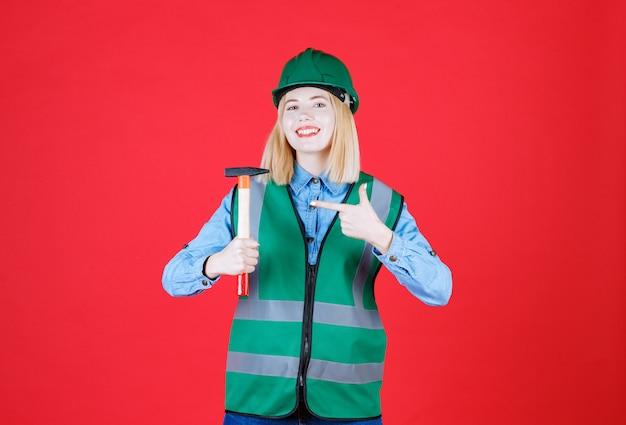 Retrato de youn vestindo uniforme e capacete faz um gesto de arma com o dedo indicador enquanto segura um martelo isolado na parede vermelha