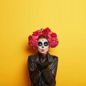 Retrato de zumbi feminino com rosto de caveira pintada, manda beijo no ar, expressa amor, comemora o dia da morte,