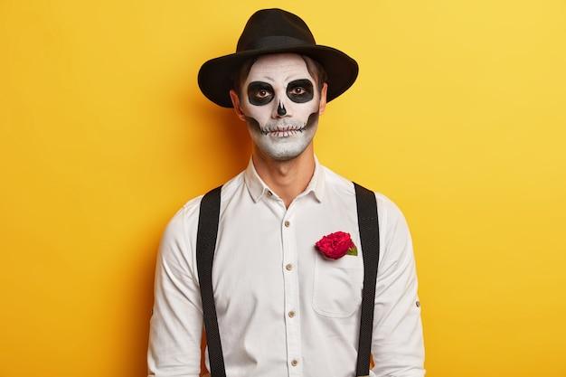 Retrato de zumbi masculino sério usa máscara de caveira, maquiagem horrível, comemora feriado mexicano, usa chapéu preto e camisa branca com suspensórios, tem uma rosa vermelha no bolso, isolada sobre fundo amarelo.