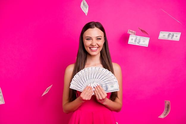 Retrato dela bonita atraente adorável alegre alegre garota de cabelos compridos segurando nas mãos uma grande quantia de dinheiro isolada em um fundo de cor rosa fúcsia vibrante brilho vívido brilhante