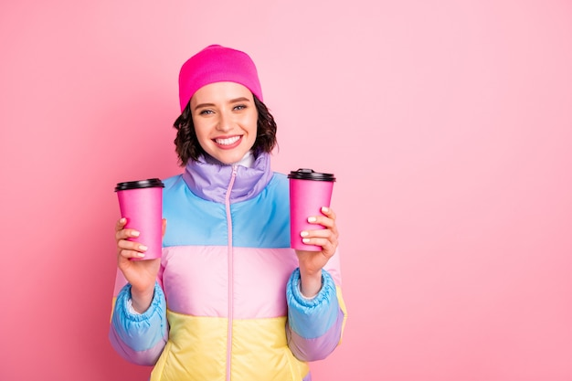 Retrato dela bonita atraente adorável alegre alegre menina segurando nas mãos duas xícaras de chá verde isoladas sobre fundo rosa
