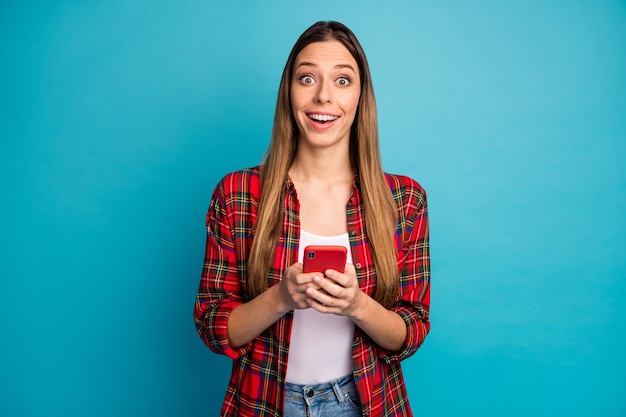 Retrato dela bonita atraente adorável feliz alegre alegre alegre garota de cabelos compridos vestindo camisa xadrez usando celular se divertindo isolado sobre fundo de cor azul brilhante brilhante vívido