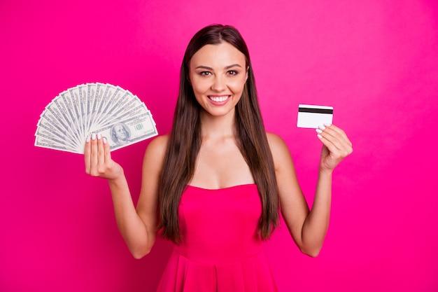 Retrato dela bonita atraente alegre confiante garota de cabelos compridos segurando na mão grande orçamento cartão atm plástico isolado em fundo de cor rosa fúcsia brilhante brilho vívido vibrante