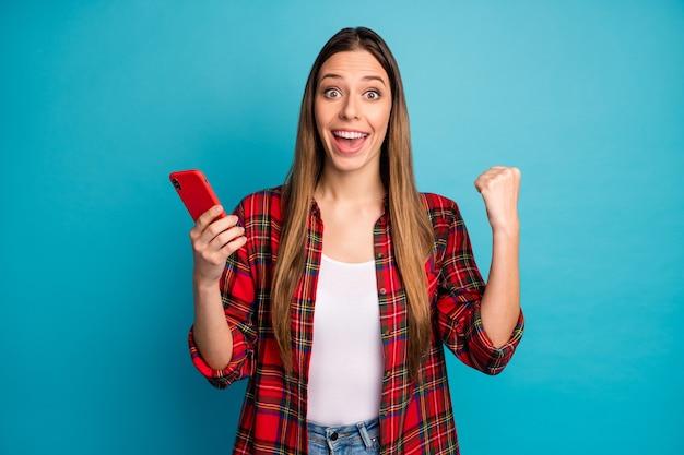 Retrato dela bonita atraente bonita adorável alegre alegre garota de cabelos compridos vestindo uma camisa xadrez usando celular se divertindo isolado sobre fundo de cor azul vibrante brilho vívido brilhante