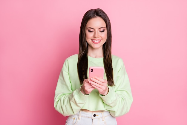 Retrato dela bonita atraente bonita adorável fofa focada alegre alegre menina de cabelos castanhos usando aplicativo de dispositivo digital 5g serviço de namoro isolado sobre fundo rosa pastel