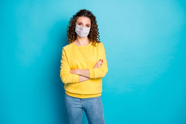Retrato dela bonita atraente confiante saudável garota de cabelos ondulados usando máscara de segurança braços cruzados medicina terapia medicare isolado brilhante brilho vívido vibrante fundo de cor azul