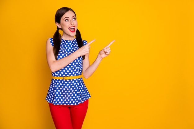 Retrato dela bonita atraente muito feliz glamourosa alegre alegre garota mostrando presente presente produto anúncio anúncio cópia espaço isolado em fundo de cor amarela vibrante brilho vívido brilhante