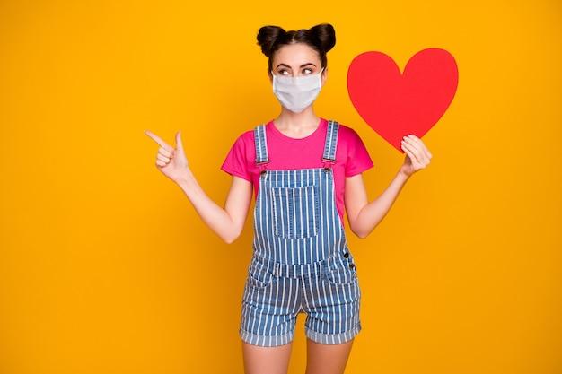 Retrato dela bonita garota atraente segurando na mão papel coração usando máscara de segurança mostrando cópia espaço mers cov infecção seguro isolado brilhante brilho vívido vibrante fundo de cor amarela