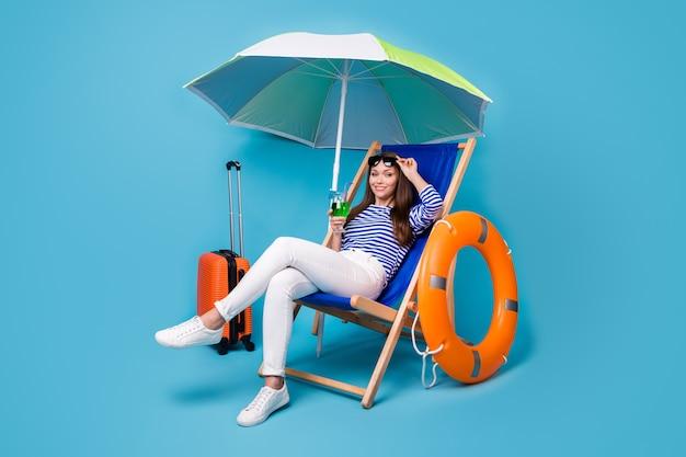 Retrato dela ela agradável atraente adorável alegre menina sentada na cadeira bebendo mojito relaxe exótico destino turístico no exterior isolado brilhante vívido brilho vibrante fundo de cor azul