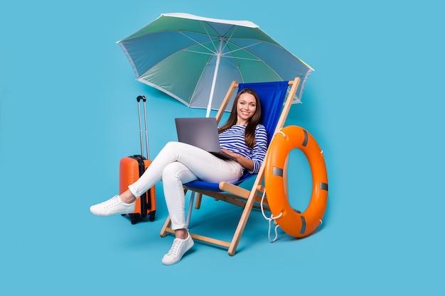 Retrato dela ela agradável atraente alegre alegre alegre menina sentada na cadeira sob o guarda-sol usando laptop resto viagem exótica excursão isolada brilhante brilho vívido vibrante fundo de cor azul