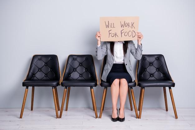Retrato dela, ela atraente, elegante, despedida, gerente executiva, sentada na cadeira, segurando um cartaz, dizendo que vai funcionar para comida palavras promo fechando o rosto isolado fundo de cor cinza pastel