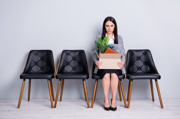 Retrato dela, ela atraente, elegante, despedida, senhora, gerente de escritório, procurador, sentado na cadeira, segurando nas mãos coisas coisas pertences empresa redução de custos isolado fundo de cor cinza pastel