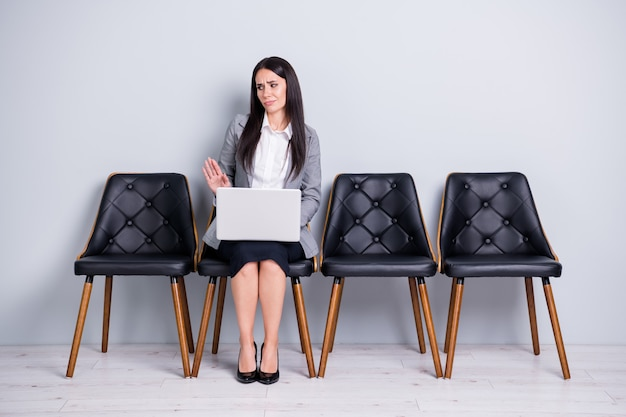 Retrato dela, ela atraente, elegante, insatisfeita, agente, corretora, sentada na cadeira, usando o laptop, recusando a proposição, graças nenhuma má ideia, isolado fundo de cor cinza pastel