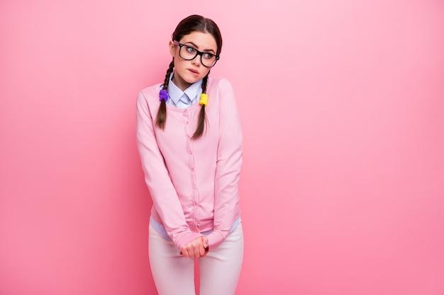 Retrato dela ela atraente inteligente inteligente modesta insegura garota de cabelos castanhos vestindo uniforme casual mordendo o lábio pensando decidindo solução isolada sobre fundo de cor rosa pastel