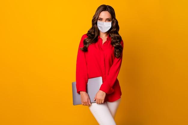 Retrato dela ela atraente linda garota de cabelos ondulados usando máscara de segurança carregando laptop manter distância social parar pandemia isolado brilhante vívido brilho vibrante fundo de cor amarela