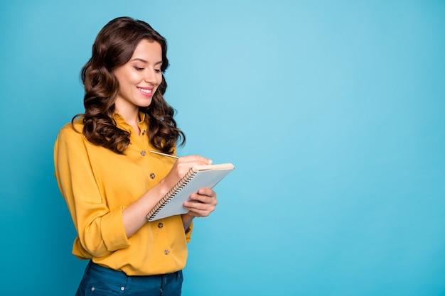 Retrato dela ela bom atraente adorável muito charmosa alegre alegre alegre garota de cabelos ondulados fazendo anotações.