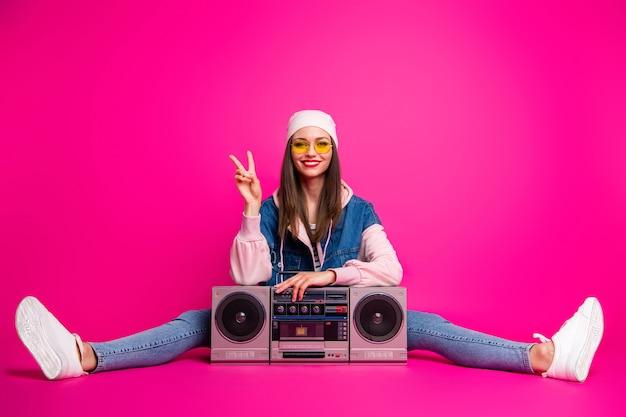 Retrato dela, ela, bonita, atraente, adorável, alegre, alegre, menina, sentada ao lado da caixa de som, mostrando um fio com sinal de v, isolado na cor rosa fúcsia vibrante de brilho vívido brilhante
