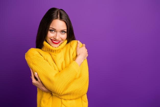 Retrato dela ela bonita atraente adorável alegre doce garota de cabelos lisos abraçando-se em um suéter quente.