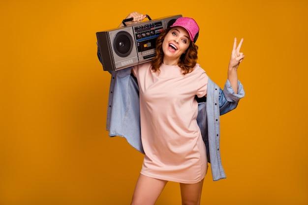 Retrato dela, ela, bonita, atraente, adorável, despreocupada, alegre, alegre, garota carregando uma caixa de som se divertindo, mostrando o sinal v isolado em um fundo de cor amarela vibrante de brilho vívido brilhante