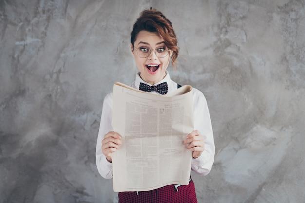 Retrato dela, ela, bonita, atraente, adorável, muito inteligente, inteligente, alegre, alegre, menina, de cabelos ondulados, lendo estatísticas periódicas de finanças isoladas no fundo da parede industrial de concreto cinza