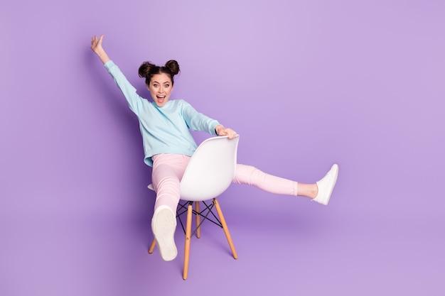 Retrato dela, ela bonita, atraente, charmoso, infantil, quadrinhos, extático, alegre, alegre, menina, sentada na cadeira, se divertindo, isolada no fundo violeta roxo lilás