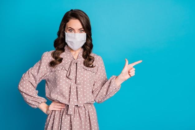 Retrato dela, ela, bonita, atraente, de cabelos ondulados, usando uma máscara de segurança de algodão, demonstrando o espaço da cópia parar, doença viral, doença, gripe, isolado, cor azul, fundo