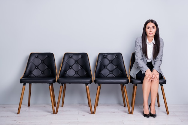 Retrato dela, ela, bonita, atraente, elegante, desesperada, frustrada, despedida, senhora, comerciante, financista, sentada na cadeira, esperando reunião, preocupando-se isolado fundo de cor cinza pastel