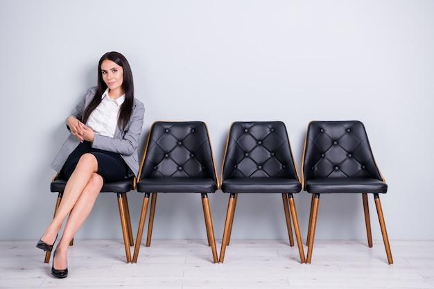 Retrato dela, ela, bonita, atraente, habilidosa, confiante, bem-sucedida, corretora imobiliária, sentada na cadeira, esperando o líder da reunião, parceiro isolado fundo de cor cinza pastel claro