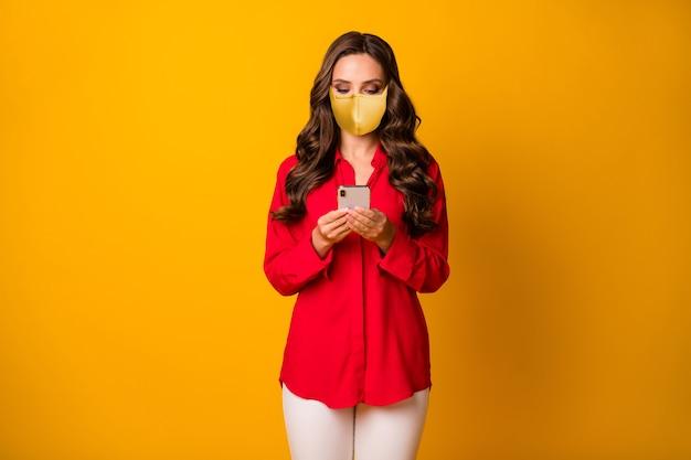 Retrato dela, ela é agradável, atraente, linda garota de cabelos ondulados usando máscara de segurança usando o dispositivo de pesquisa mers cov infecção sintoma isolado brilhante vívido brilho vibrante fundo de cor amarela