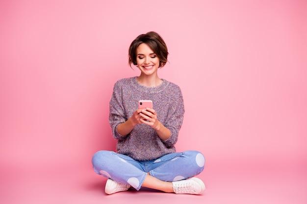 Retrato dela, ela é legal, atraente, adorável, charmosa, muito fofa, alegre, alegre, cabelos castanhos, menina, sentada, usando o aplicativo celular 5g, isolado sobre a parede rosa